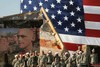 Soldiers Gathered In Front of a Huge American Flag and a Mural of Soldiers. clipart