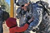 Smiling Soldier Picks Up an Iraqi Child. clipart
