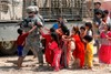 Iraqi Children, Dressed in Colorful Clothes, Following a U.S. Soldier. clipart